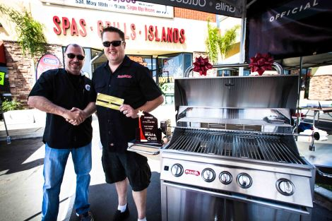 Mark Nureddine, President and CEO of Bull Outdoor Products presents Mark McGrath of the Porkateers with his ticket to The WOrld Food Championships and a new Bull Angus Grill Cart